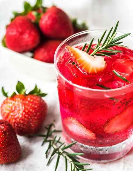 strawberries near clear rocks glass